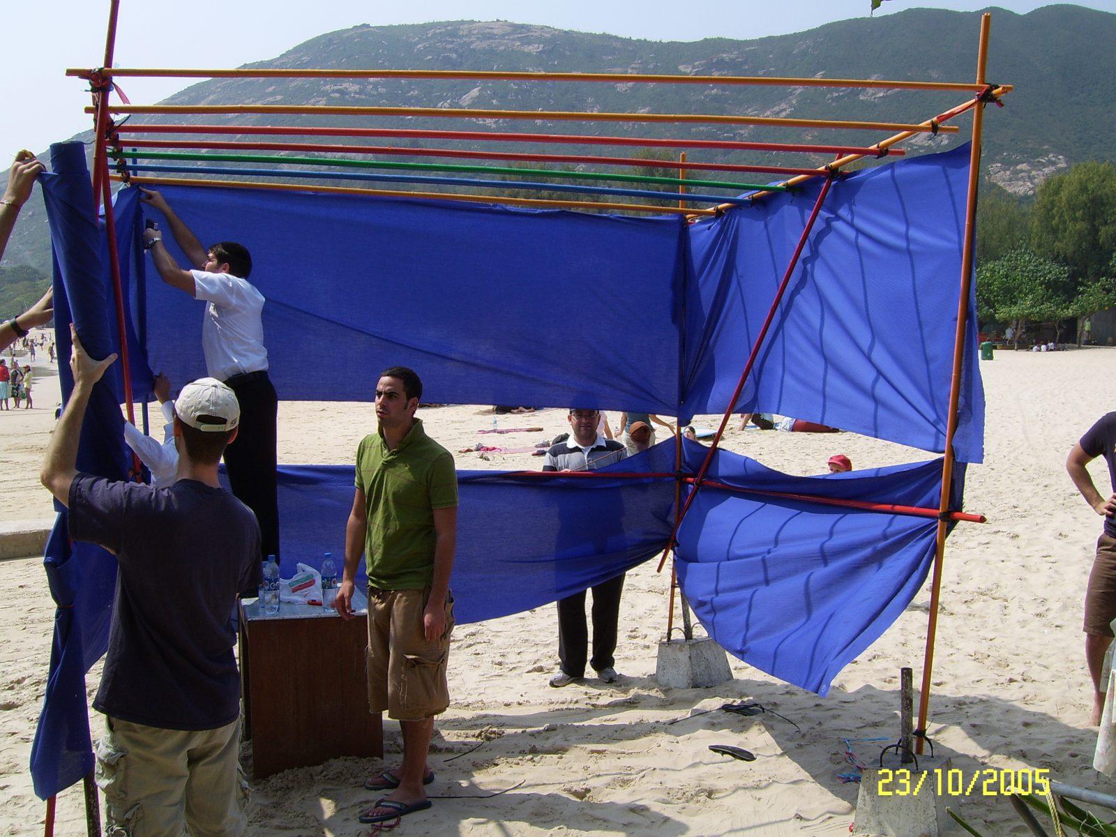 חברי הקהילה היהודית בבניית סוכה על חוף הים